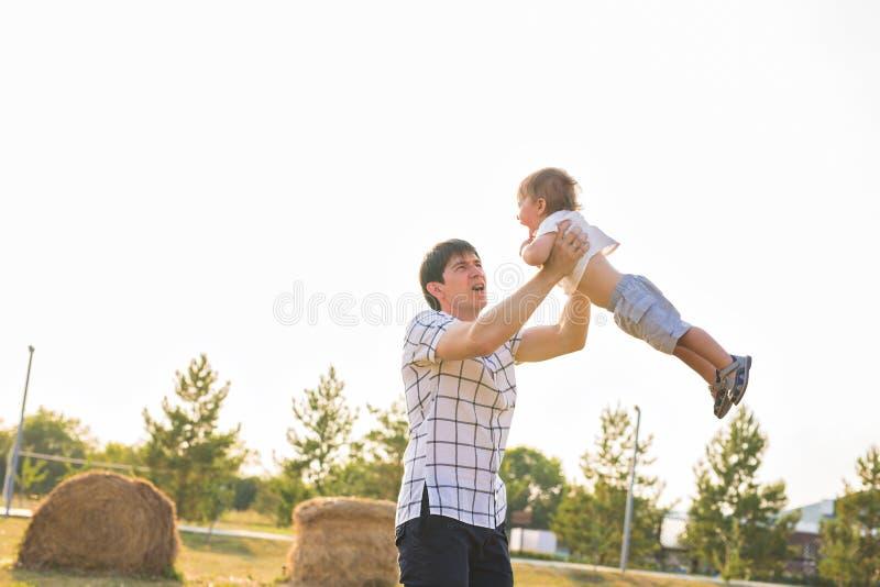 Fader och son som spelar på fältet på dagtiden Folk som har roligt utomhus Begrepp av den vänliga familjen arkivbilder