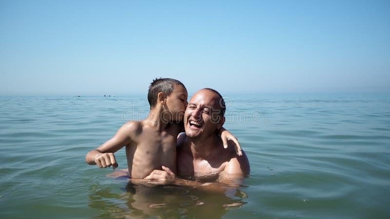 Fader och son som spelar på för strand livsstilen för stående tillsammans den roliga lyckliga arkivbild