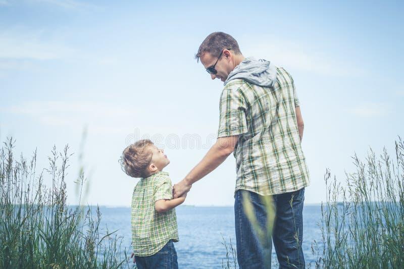 Fader och son som spelar på parkera nära sjön på dagtiden royaltyfria bilder