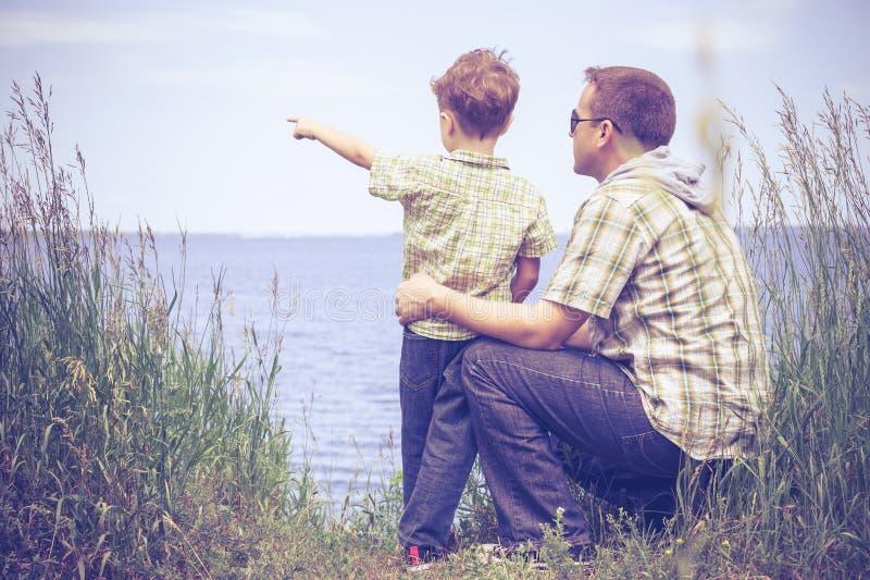 Fader och son som spelar på parkera nära sjön på dagtiden arkivfoton