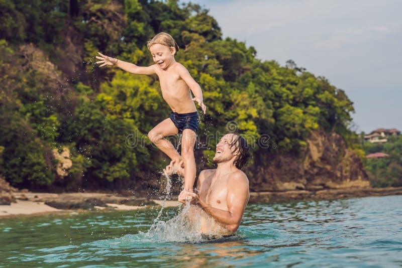 Fader och son som spelar på stranden på dagtiden arkivbild