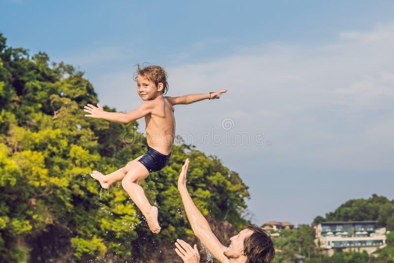 Fader och son som spelar på stranden på dagtiden royaltyfri bild