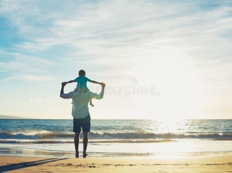 Fader och son som spelar på stranden på solnedgången royaltyfria bilder