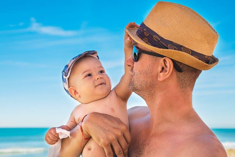 Fader och son som spelar på stranden på tiden för sommardag royaltyfri fotografi