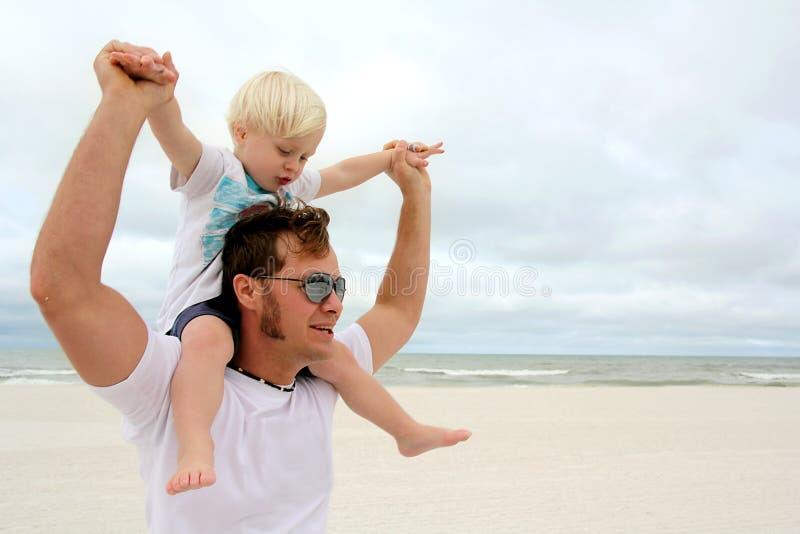 Fader och son som spelar på stranden vid havet arkivbilder