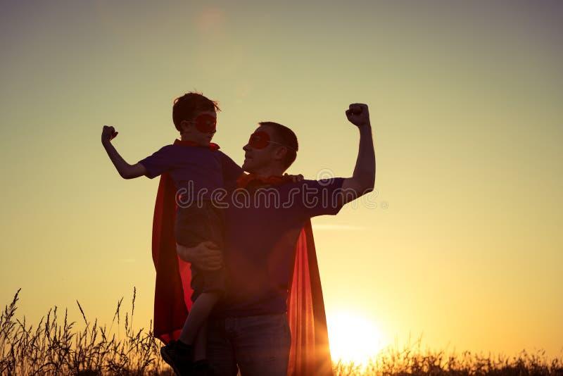 Fader och son som spelar superheroen på solnedgångtiden arkivfoto