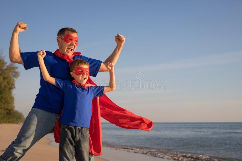 Fader och son som spelar superheroen p? stranden p? dagtiden royaltyfria bilder
