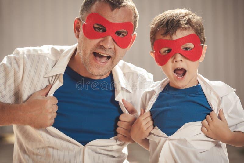 Fader och son som spelar superheroen utomhus på dagtiden arkivbilder