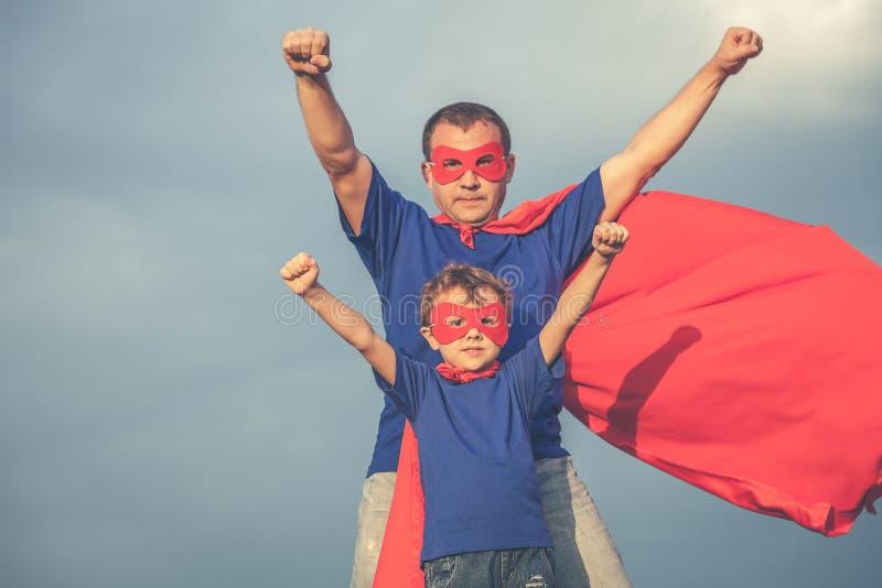 Fader och son som spelar superheroen utomhus på dagtiden royaltyfri bild