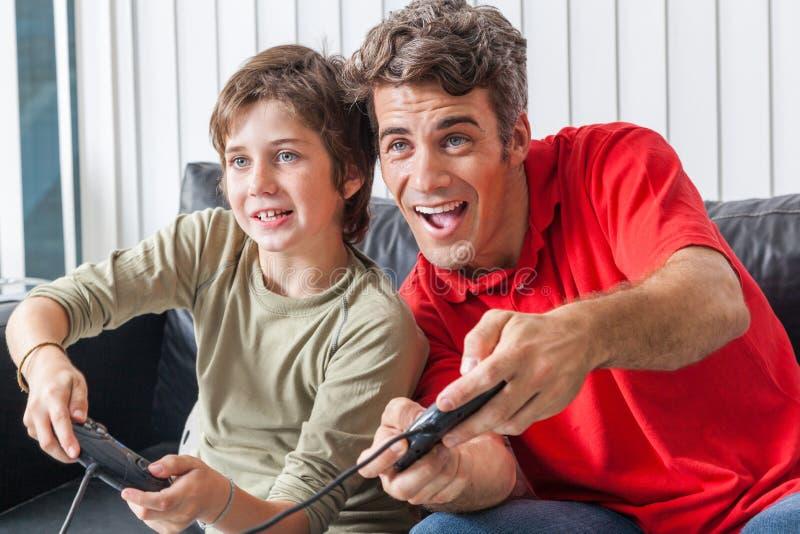 Fader och son som spelar videospelet royaltyfria bilder