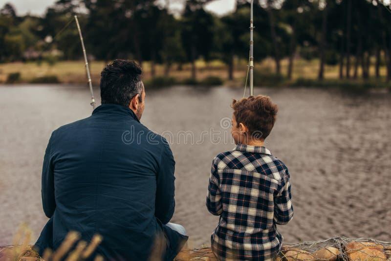 Fader och son som spenderar tid som fiskar tillsammans i en sjö royaltyfri foto
