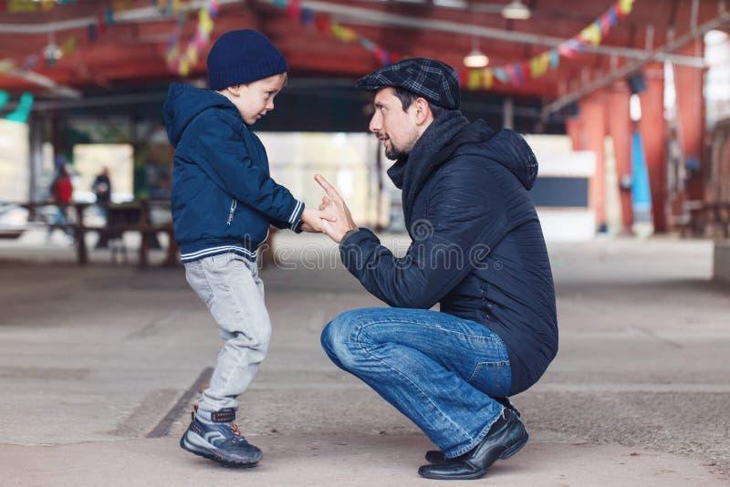 Fader och son som till varandra talar rymma händer som ser de arkivbilder