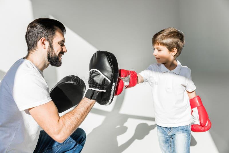 Fader och son som tillsammans boxas royaltyfria bilder