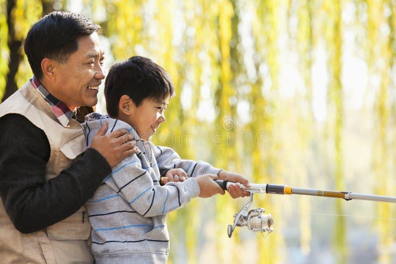 Fader och son som tillsammans fiskar på sjön arkivfoton
