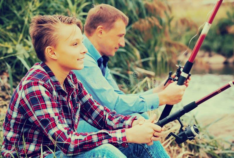 Fader och son som tillsammans fiskar på sjön arkivbild