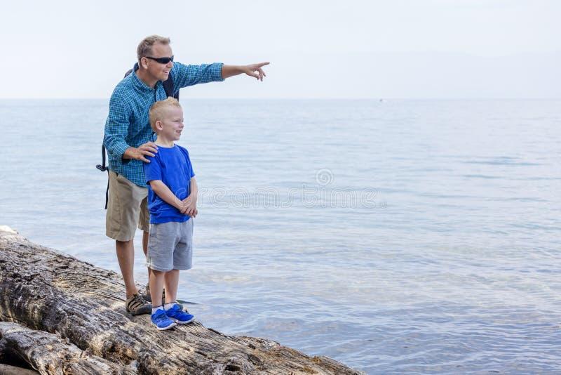 Fader och son som tillsammans fotvandrar längs en scenisk sjö fotografering för bildbyråer
