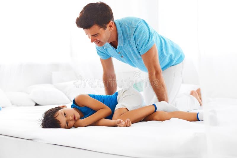 Fader och son som tillsammans kopplar av på säng arkivbilder
