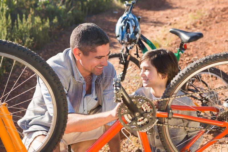 Fader och son som tillsammans reparerar cykeln royaltyfria bilder
