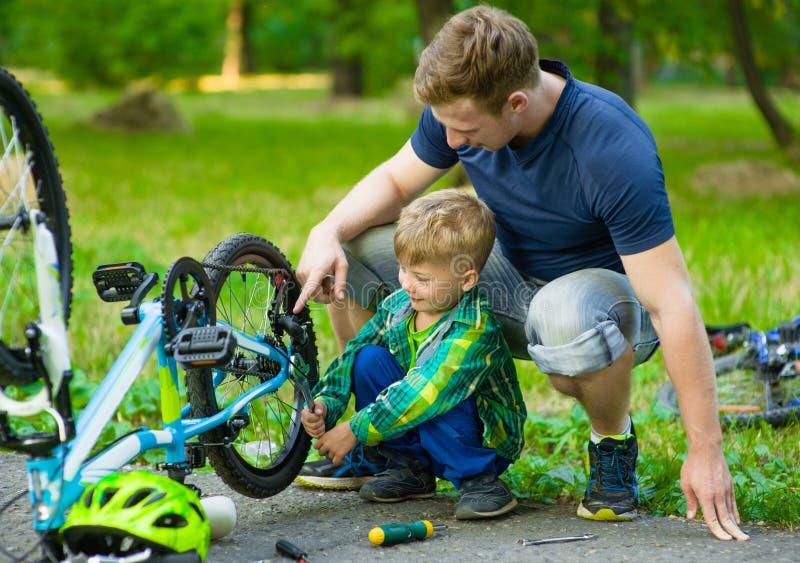 Fader och son som tillsammans reparerar cykeln royaltyfri foto