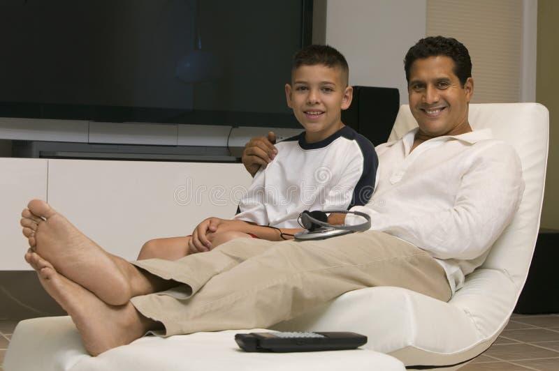 Fader och son som tillsammans sitter på stol i vardagsrumstående royaltyfria bilder