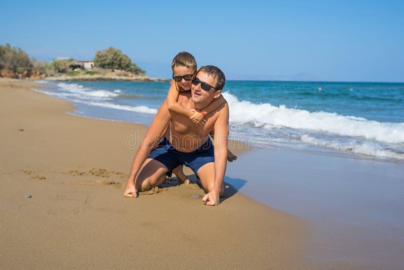 Fader och son som tillsammans spelar på stranden och att ha den kvalitets- familjen Tid Grekland arkivbilder
