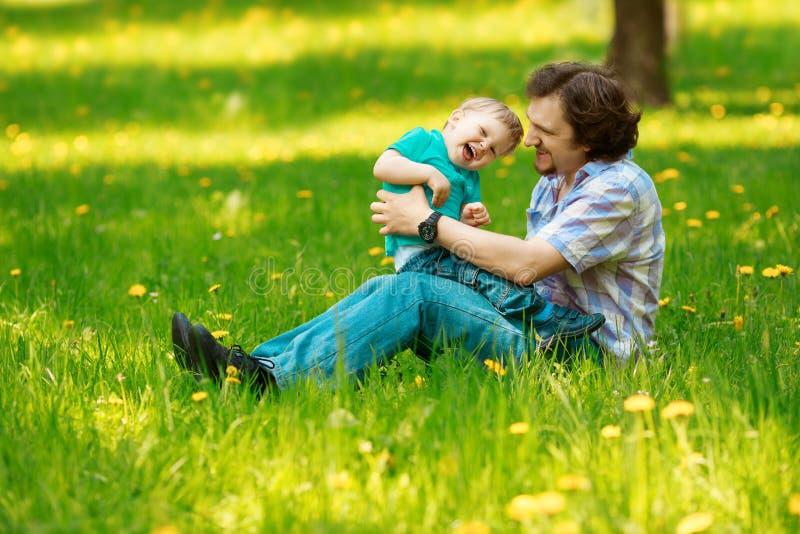Fader och son som tillsammans spenderar tid på en solig dag Lycklig litt royaltyfri fotografi