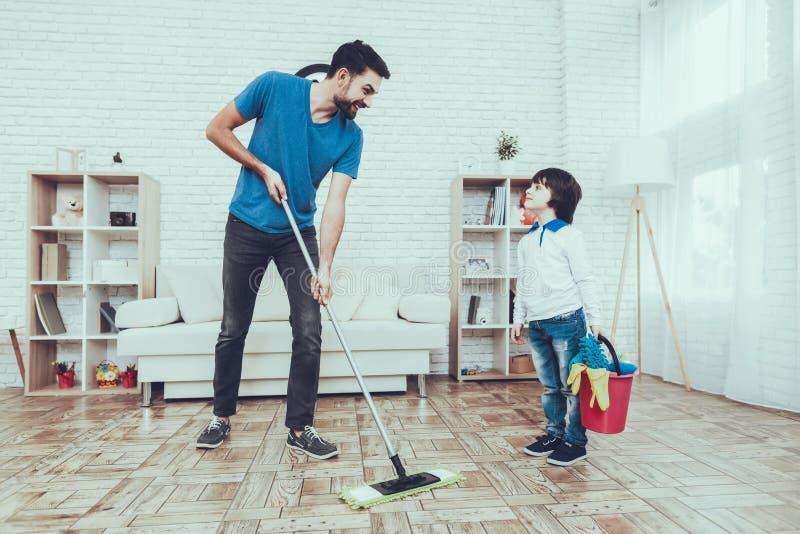 Fader och son som tvättar golvet royaltyfria foton