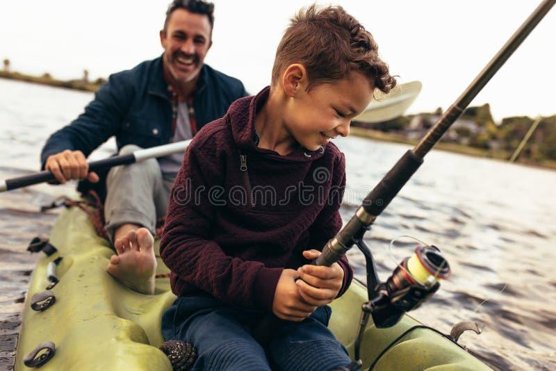 Fader och son som tycker om att fiska i sjön royaltyfri fotografi
