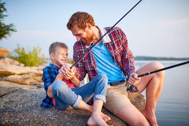 Fader och son som tycker om att fiska tillsammans royaltyfri foto