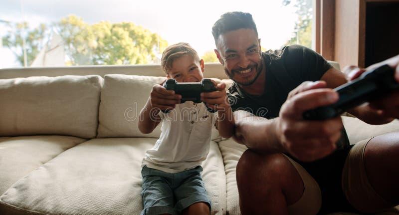 Fader och son som tycker om spela videospelet arkivbilder