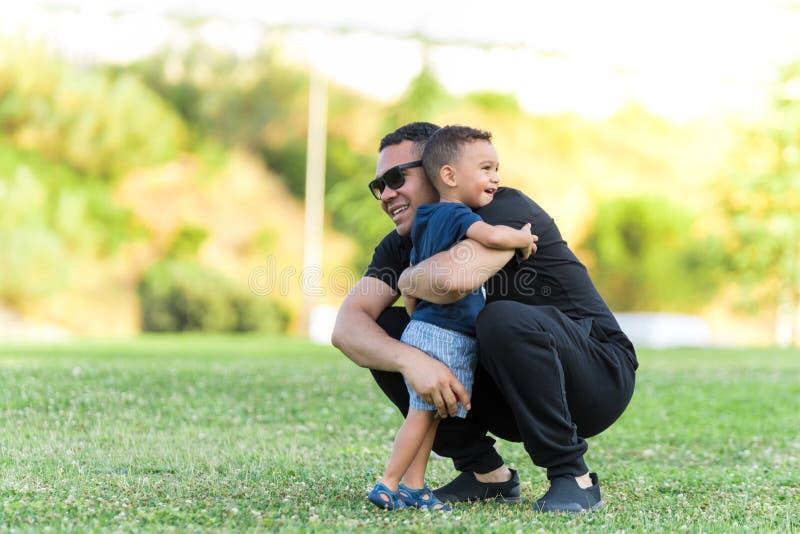 Fader och son som utomhus kramar arkivbild
