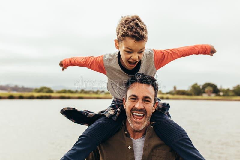 Fader och son som utomhus spelar nära en sjö royaltyfri foto
