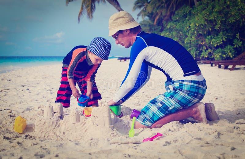 Fader- och sonbyggnadssandslott på stranden arkivfoto