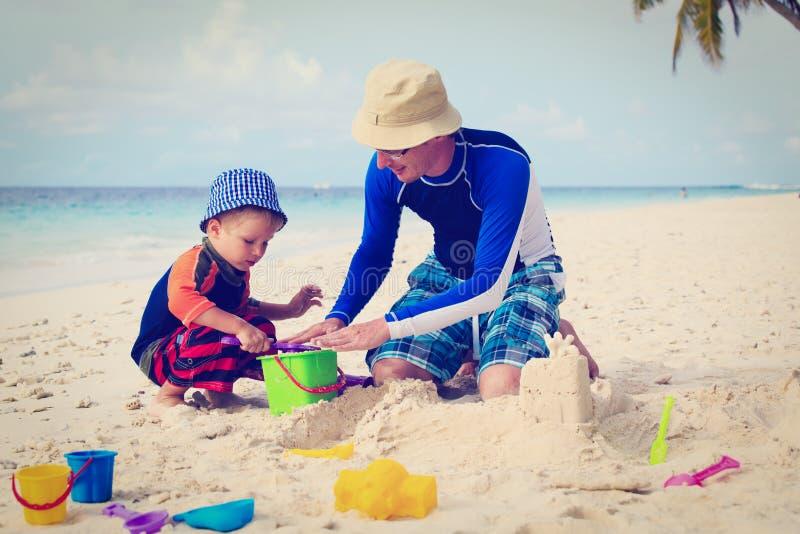 Fader- och sonbyggnadssandslott på stranden fotografering för bildbyråer