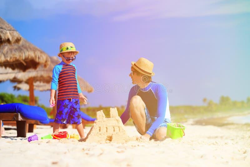 Fader- och sonbyggnadssandslott på stranden royaltyfria foton