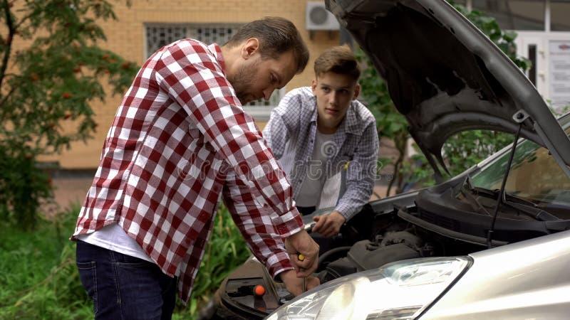 Fader- och sonfixandebil, farsa som undervisar den tonåriga pojken att reparera motorn, förebild royaltyfri bild