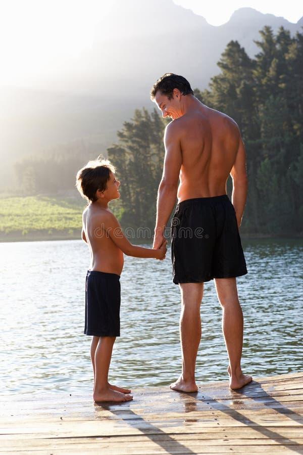Fader- och sonholdingen hands standing på bryggan royaltyfri bild