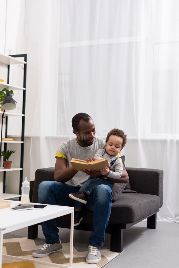 fader- och sonläsebok tillsammans på soffan royaltyfria foton
