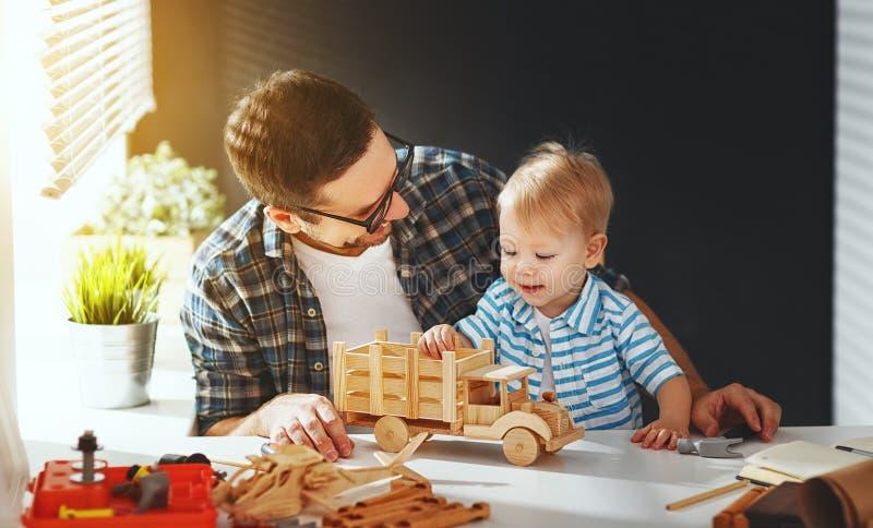 Fader- och sonlitet barnhopsamlingen tillverkar en bil ut ur trä och spelar royaltyfria bilder