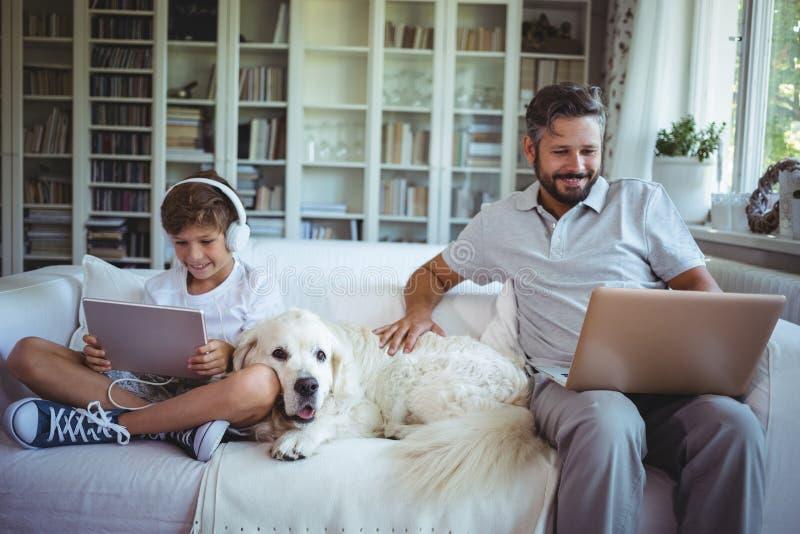 Fader- och sonsammanträde på soffan och använda den digitala minnestavlan och bärbara datorn royaltyfri foto