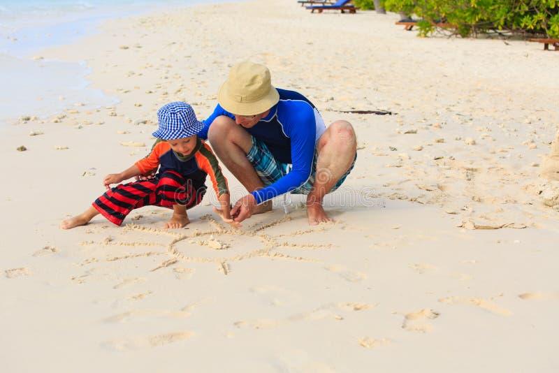 Fader- och sonteckningssol på stranden royaltyfri foto