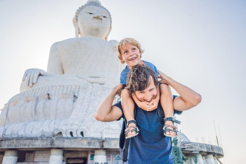 Fader- och sonturister på den stora Buddhastatyn Byggdes på en hög bergstopp av Phuket Thailand kan ses från a royaltyfri fotografi