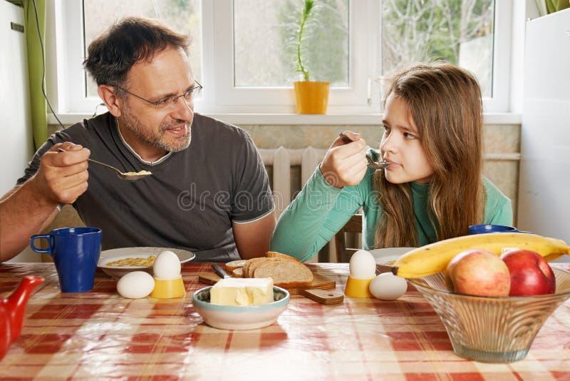 Fader och tonårs- dotter som har frukosten i köket på helgmorgonen royaltyfri foto
