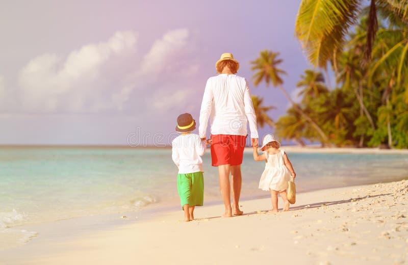 Fader och två ungar som går på stranden arkivbilder