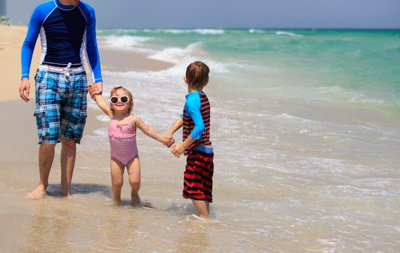 Fader och två ungar som går på stranden royaltyfria foton