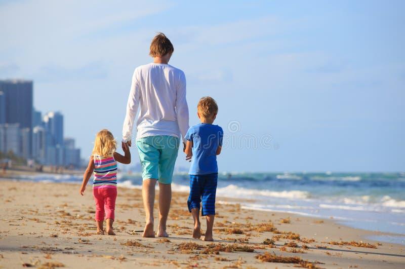Fader och två ungar som går på stranden royaltyfria bilder