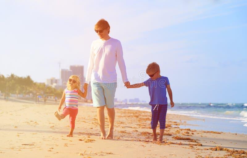 Fader och två ungar som går på stranden fotografering för bildbyråer