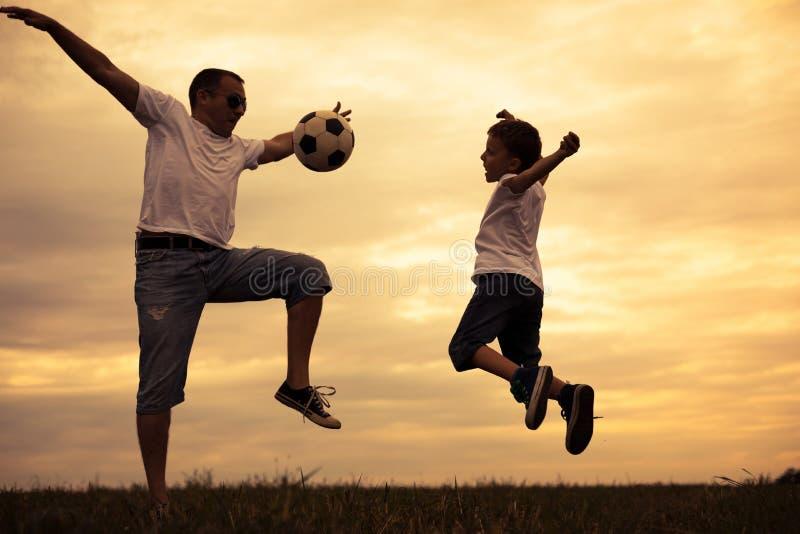 Fader och ung liten son som spelar i fältet med fotbolllodisar royaltyfria bilder