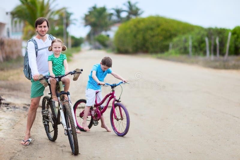 Fader och ungar på cyklar arkivbild