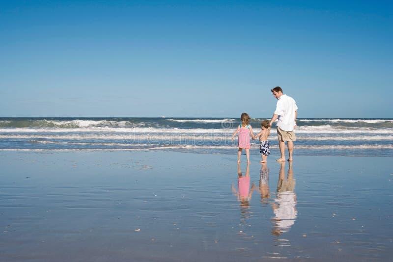 Fader och ungar på en strand royaltyfri foto